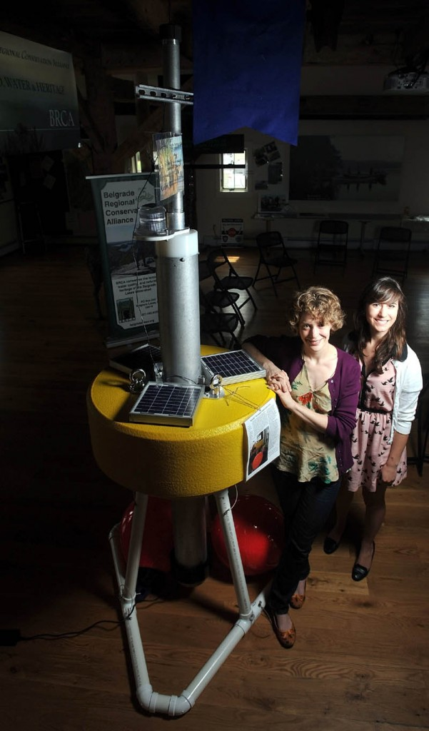 """Denise Bruesewitz, an associate professor at Colby College, and Theresa Petzoldt, 21, an environmental studies major, stand next to """"Goldie,"""" a research buoy, at the Maine Lakes Resource Center in Belgrade on Friday."""