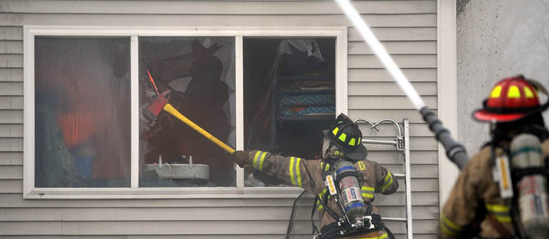Firefighters from Waterville, Winslow and Fairfield battle a fire at 10 Maple St. in Fairfield on Tuesday.