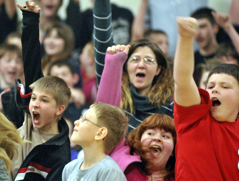 Warsaw Middle School sixth-grade students, DJ Neil, left, Anthony Dow, left center, Ashley Humphrey, right center, and Cody Marquis, right, cheer during an assembly recognizing music teacher Marisa Weinstein.