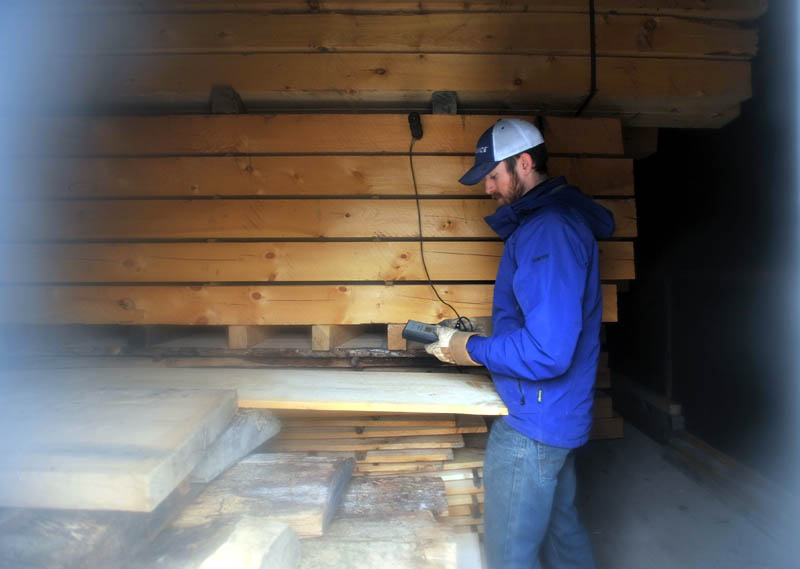 Josh Saltmarsh checks the moisture content of lumber in the dehumidification kiln at The Wood Mill of Maine, on Mercer Road in Mercer, on Friday.