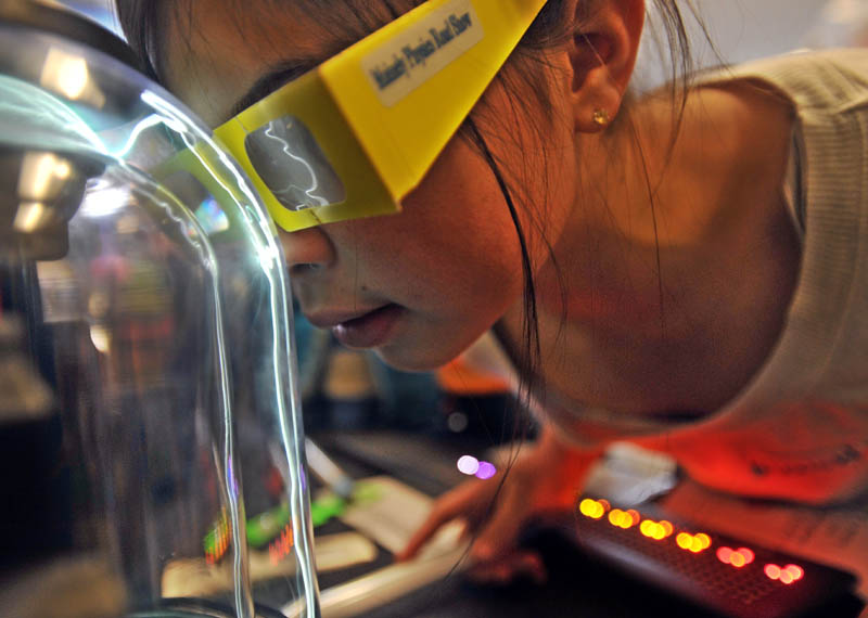 Alexis West, 10, plants her nose on the plasma ball in the first Science, Technology, Engineering and Math Day, at Albert S. Hall School in Waterville on Friday.