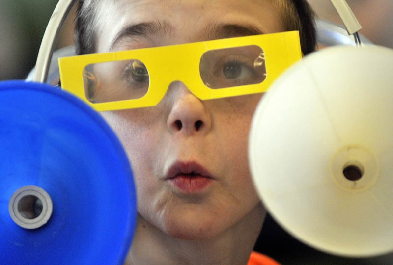 Chase Perkins, 11, reacts after listening to a variety of sounds in his sound amplification head set during the physics lessons in the first Science, Technology, Engineering and Math Day at Albert S. Hall School in Waterville on Friday.