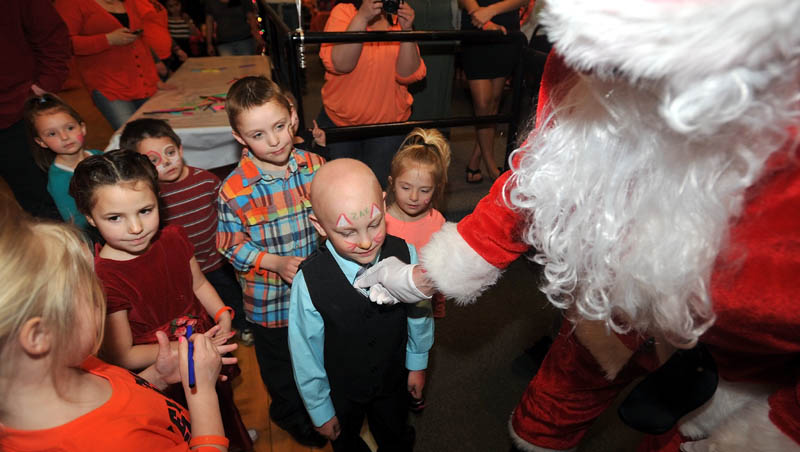 Zachary Korbet, 4, is greeted by Santa Claus at Champions in Waterville on Saturday. Korbet was diagnosed with leukemia in January and is receiving treatment at Maine Children's Cancer Program in Scarborough. Santa's visit was part of a benefit to help offset treatment costs. The Christmas theme was catered to Zach's affinity for the holiday.