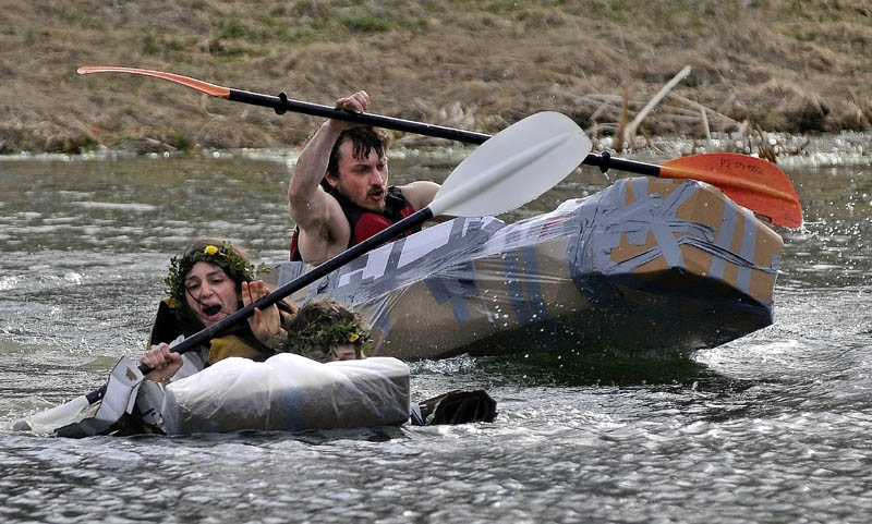 Hannah Rhea, 20, left, paddles with her partner, Mike Froehly, 20, not seen, ahead of Colby Smith, 28, back, in the first heat of the cardboard kayak race at Unity College on Friday. Students had one hour to fabricate kayaks from cardboard, tape and plastic.