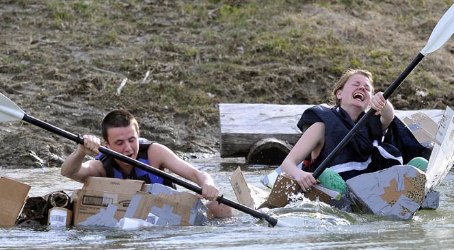 Chris Iacozzi, 18, left, and Summer Nay, 20, race in the third heat of the first cardboard kayak race at Unity College on Friday.