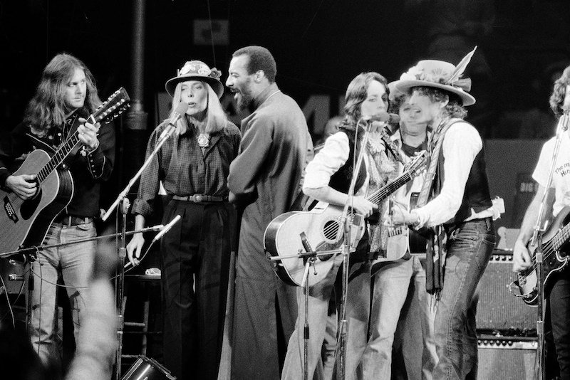 In this Dec. 1975 file photo, musicians Roger McGuinn, Joni Mitchell, Richie Havens, Joan Baez and Bob Dylan perform the finale of the The Rolling Thunder Revue, a tour headed by Dylan.  (AP Photo, File)
