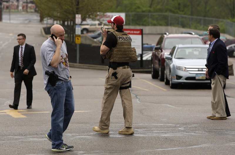 Sheriff's Deputies and other officials stand outside LaSalle High School, Monday, April 29, 2013, in Cincinnati where a high school student pulled out a gun and shot himself in a classroom on Monday. The Hamilton County sheriff's office says the youth was taken to a hospital with a self-inflicted wound. They say there apparently was no threat to other students at the private school. (AP Photo/Cincinnati Enquirer, Glenn Hartong)