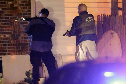 Police officers aim their weapons Friday in Watertown, Mass., where residents of the Boston suburb have been advised to keep their doors locked and not let anyone in.