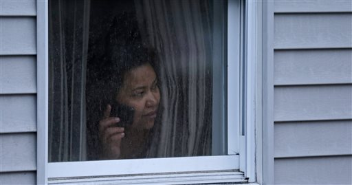 A woman looks out a window at her home as police start to search an apartment building while looking for a suspect in the Boston Marathon bombings in Watertown, Mass., on Friday.