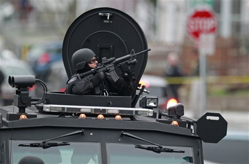 Police in tactical gear and riding in an armored police vehicle surround an apartment building in Watertown, Mass., on Friday as they hunt for the surviving suspect in the Boston marathon bombings.