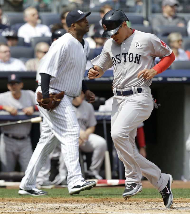Boston Red Sox runner Jacoby Ellsbury, right, scores in front of New York Yankees starting pitcher CC Sabathia, left, on Dustin Pedroia's second-inning, RBI single in an Opening Day baseball game at Yankee Stadium in New York on Monday.