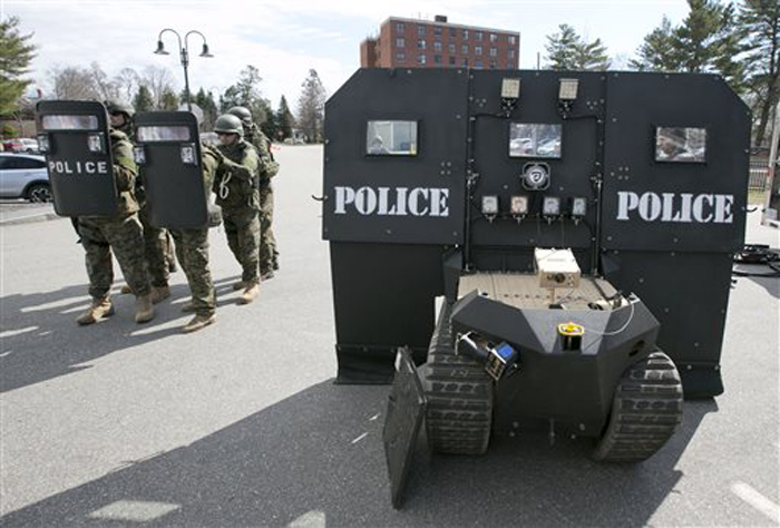 A team of police line up behind hand-held bulletproof shields, showing the relative lack of protection compared to a SWAT robot, right, during a demonstration for the media in Sanford on Thursday.