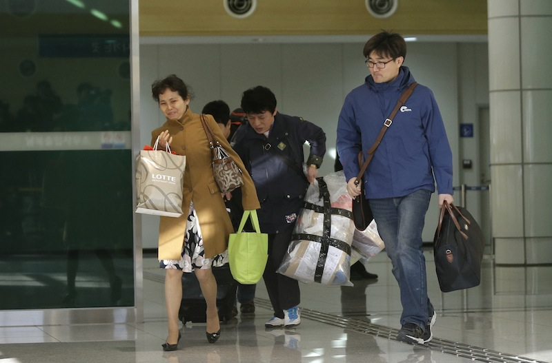 South Koreans arrive with their belongings from North Korea's Kaesong at the customs, immigration and quarantine office near the border village of Panmunjom, that has separated the two Koreas since the Korean War, in Paju, north of Seoul, South Korea, Tuesday, April 9, 2013. A few hundred South Korean managers, some wandering among quiet assembly lines, were all that remained Tuesday at the massive industrial park run by the rival Koreas after North Korea pulled its more than 50,000 workers from the complex. Others stuffed their cars full of goods before heading south across the Demilitarized Zone that divides the nations. (AP Photo/Lee Jin-man)