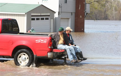 A pickup truck from the Grafton Marina takes two men across a flooded section of marina entrance road on Monday in Grafton, Ill. Floodwaters from the Mississippi River have closed the main entrance forcing residents to use a back road away from the river.