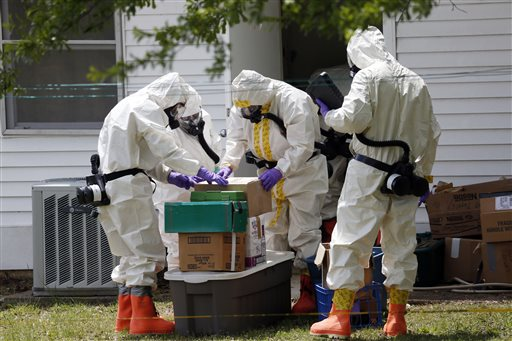 Federal agents wearing hazardous material suits and breathing apparatus inspect the home and possessions of Paul Kevin Curtis in Corinth, Miss., on Friday. Curtis is in custody under the suspicion of sending letters covered in ricin to President Barack Obama and U.S. Sen. Roger Wicker, R-Miss.