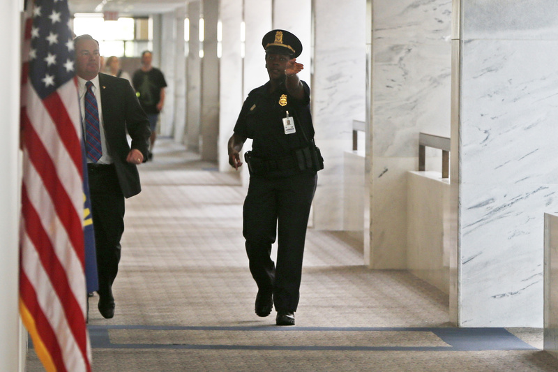 A Capitol police officer tells people to clear the hallway on the third floor of the Hart Senate Office building after suspicious packages were discovered on Capitol Hill in Washington on Wednesday.