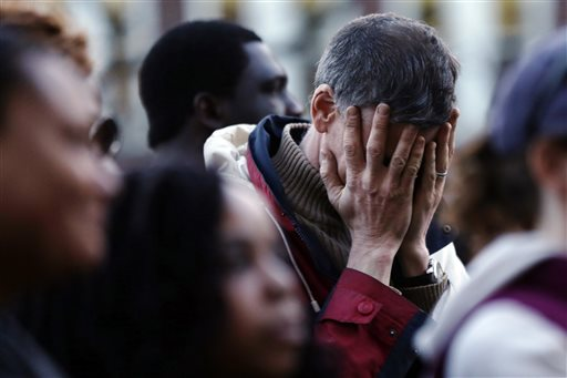 In this Wednesday photo, a mourner reacts during a candlelight vigil at City Hall in Cambridge, Mass. in the aftermath of Monday's Boston Marathon explosions.