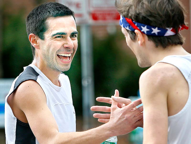 Winner Louie Luchini of Ellsworth, left, congratulates second-place finisher Chris Harmon of Scarborough after finishing the 84th Patriots Day 5-mile race in Portland on Sunday.