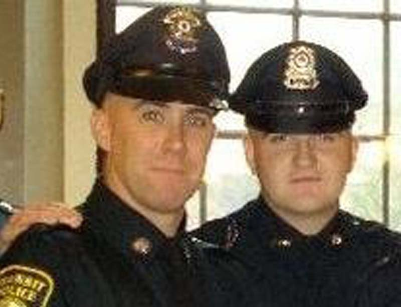 In this 2010 photo provided by the Massachusetts Bay Transportation Authority, Richard Donohue Jr., left, and Sean Collier pose together for a photo at their graduation from the Municipal Police Officers' Academy.