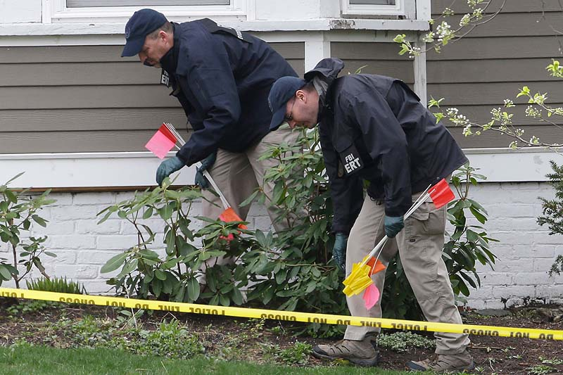 Investigators on Saturday work near the location where the previous night a suspect in the Boston Marathon bombings was arrested in Watertown.