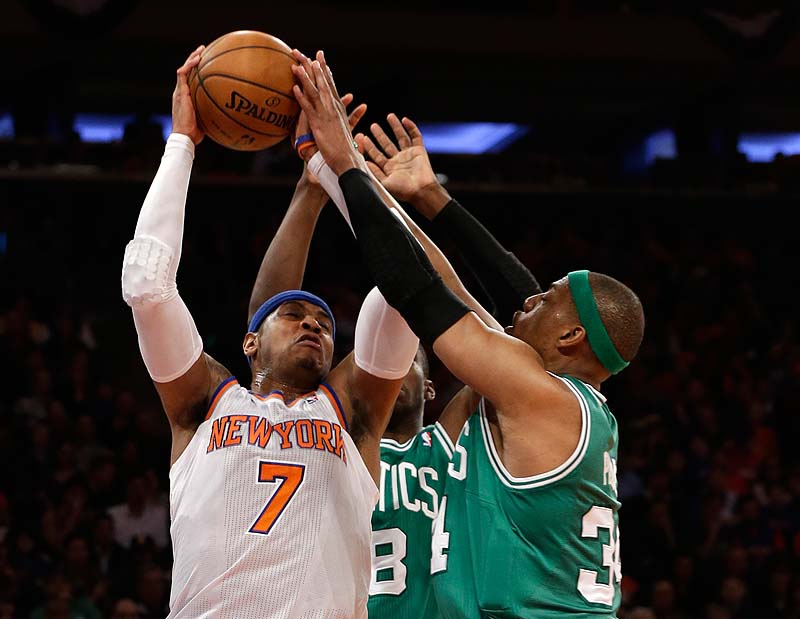 Carmelo Anthony of the Knicks fends off Boston's Jason Terry, 8, and Paul Pierce in the first half of Saturday's playoff game at New York.