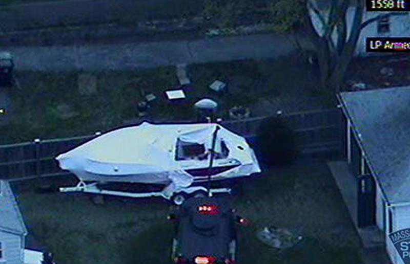 This image made available by the Massachusetts State Police shows a police vehicle probing the boat where 19-year-old Boston Marathon bombing suspect Dzhokhar Tsarnaev was hiding in Watertown, Mass. He was pulled, wounded and bloody, from the boat parked in the backyard of a home in the Greater Boston area.