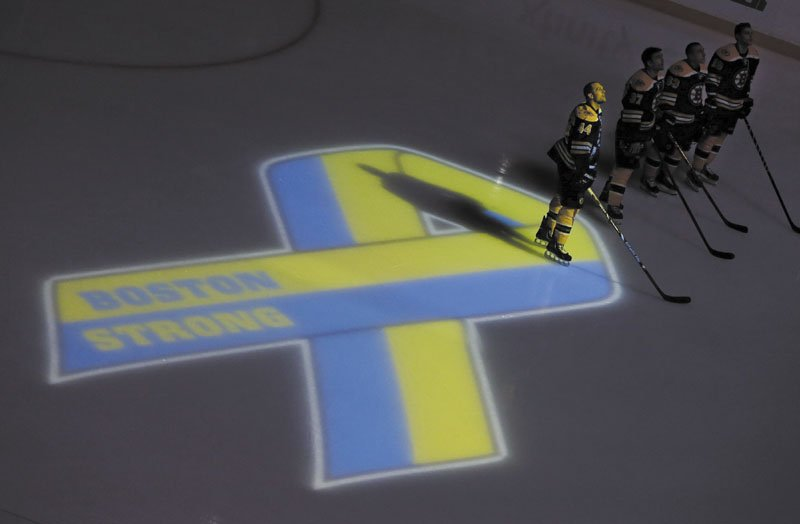 BOSTON STRONG: Boston Bruins players, including defenseman Dennis Seidenberg (44), stand next to a ribbon projected onto the ice at TD Garden on Wednesday in Boston during a pregame ceremony in the aftermath of Monday's Boston Marathon bombings. TD Garden