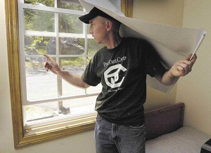 Harvey Chesley, then-director of Pine Tree Camp, shows a window that was carefully forced open, but not broken, to get at food in one of the camp's buildings in 2005.