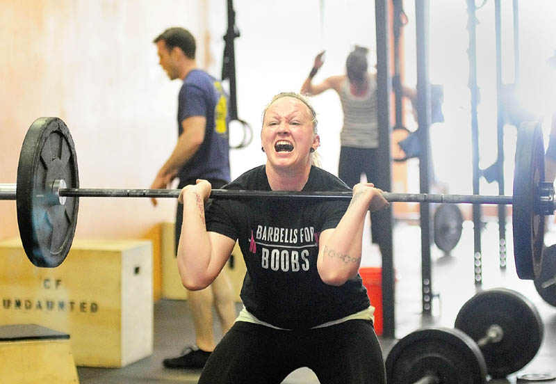 "HARD WORK: Ali McLaughlin, of Winslow, does a squat clean while performing the ""Klepto"" Hero WOD on Saturday at CrossFit Undaunted in Augusta. The workout is named after Major David ""Klepto"" Brodeur, a fighter piolot killed in Afghanistan."