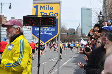 "Onlookers watch as runners cross the ""1 Mile To Go"" marker shortly after 12 p.m. Monday at the Boston Marathon. Just before 3 p.m., two bombs exploded 12 seconds apart at the marathon finish line, killing three and injuring 176 others."
