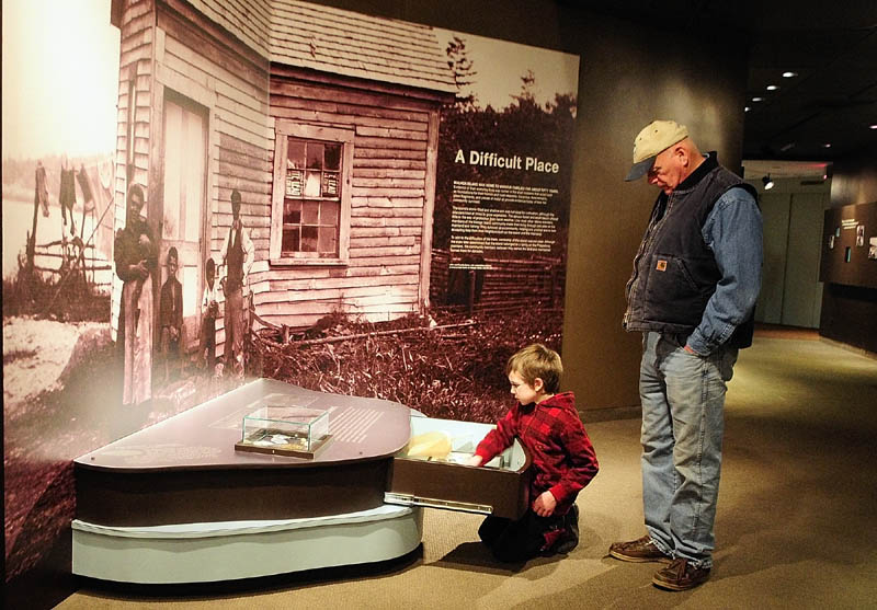 """Ciaran Seltsman, 9 of Augusta, left, and his grandfather, Robert Seltsman, of Leeds, look at items in a drawer on Thursday in the """"Malaga Island, Fragmented Lives"""" exhibition at the Maine State Museum in Augusta."""