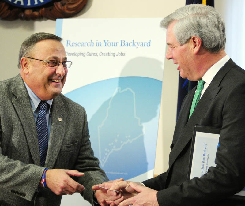 """Gov. Paul LePage, left, presents an """"Open for Business"""" business card to PhRMA CEO John Castellani at a news conference Friday at the State House in Augusta. A new report says the more than 550 clinical trials of new medicines in Maine since 1999 support thousands of jobs and millions of dollars in federal and state taxes."""