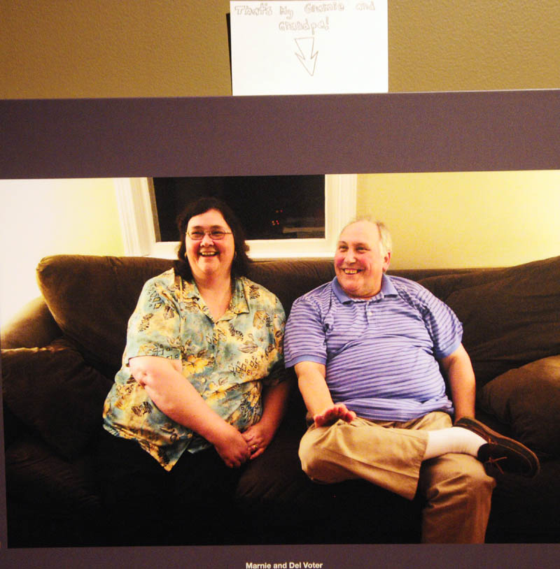 """A note above a photo of Malaga descendant Marnie Voter, left, and her husband, Del Voter, in the """"Malaga Island, Fragmented Lives"""" exhibition, reads """"That's My Gramie and Grandpa,"""" at the Maine State Museum in Augusta."""