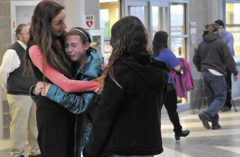 Deb McIntyre, left, comforts Katelin Lewis, 11, center, a sixth-grader at Mount View Middle School, in the hall of Mount View High School following the community forum on suicide prevention and grieving on Thursday evening.