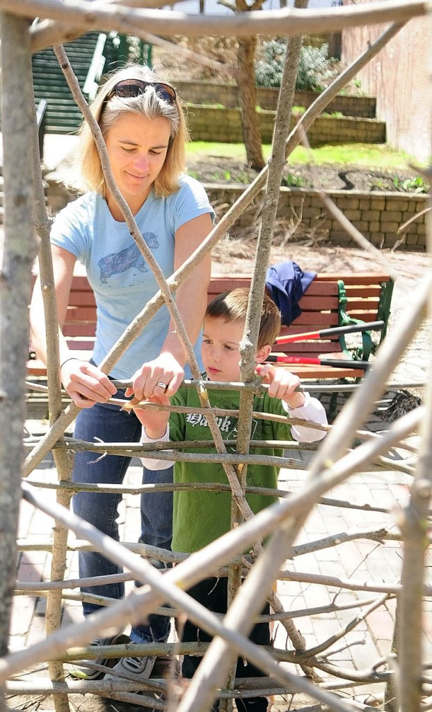 "Jen Wright, left, and her son, Sawyer, help Gardiner's 2013 Artist in Residence, Susan Perrine, build a twig sculpture out of locally sourced materials Saturday at Johnson Hall Mini Park in Gardiner. Perrine began weaving twig sculptures as a way to teach weaving on a large scale. Perrine's work reflects on her connection to the natural environment. ""I grew up on a farm and have always spent a lot of time outdoors, walking the fields and woods near home,"" she said. ""I try to use methods and materials to reflect the connection I feel towards the natural environment."" Susan will be showing at Artwalk after the reception in the park where her sculpture will reside."