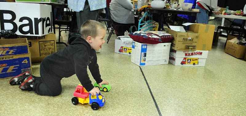 Riley Lenhart, 3 of Gardiner, takes a test drive with some toy trucks that his mother, Tona Libby, bought for him on Saturday at an charity indoor yard sale in the Knights of Columbus Council 1299 Hall in Gardiner. It was a fundraiser for Jacob Lamoreau to get hearing aids, and the Knights group was donating funds from concession and table rentals.