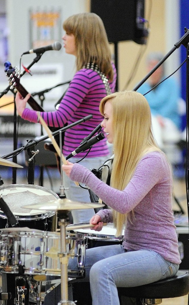 Kristen Veayo, top, and her sister, Katherine Veayo, perform a song during a school assembly on Wednesday at Windsor Elementary School. The Hall-Dale High School students, who perform as The Veayo Twins, spoke about dealing with bullying between performing covers of hit songs along with several of their own compositions.