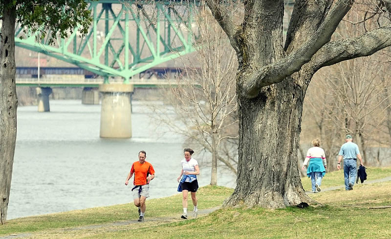 Runners and walkers make their way along the banks of the Kennebec River on the Augusta Greenway trail, on the Kennebec arsenal grounds, on Friday.