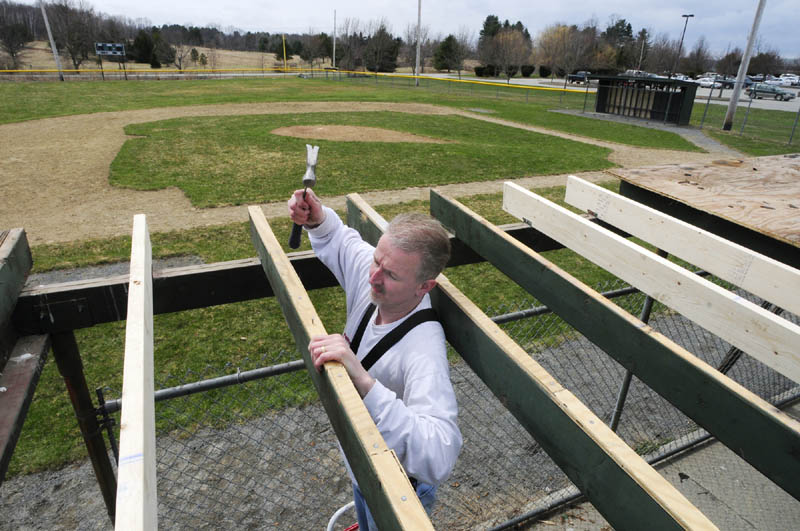 Norman Barbeau and other volunteers repair a dugout roof at Rivelli Field on Friday in Augusta. The field is used by Augusta Little League, whose season will open in two weeks, on May 4.