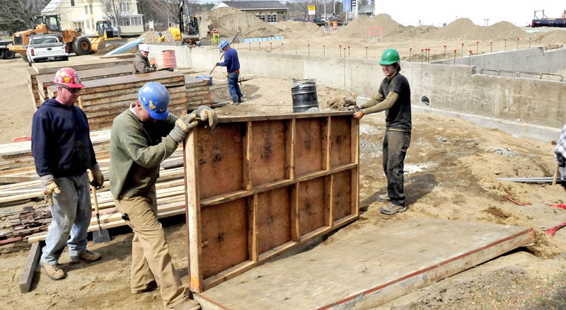 Workers build foundation walls for the new Advance Auto Parts being built on Madison Avenue in Skowhegan on Tuesday.