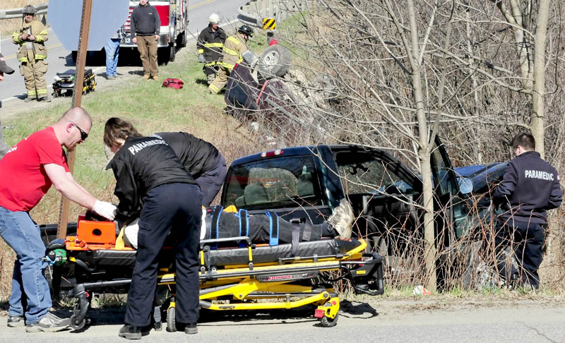 Rescue workers remove an injured occupant of a truck as another injured person in the background is removed from an SUV following an accident on Route 43 in Cornville on Thursday.