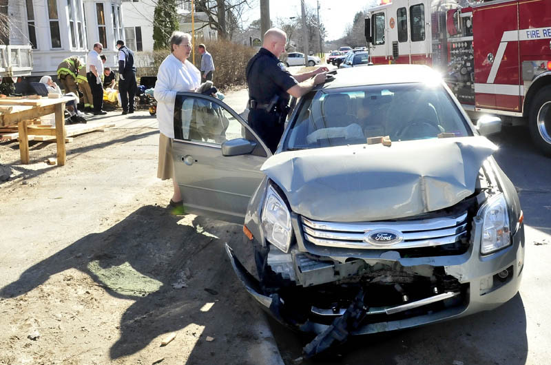 Waterville police officer Tim Hinton collects information from the vehicle that contained Sister Josephine Roney, left, as two other sisters in background are treated and transported to the hospital following an accident on Silver Street in Waterville on Wednesday. Sister Josephine Roney said the nuns vehicle struck a parked truck near the Servants of the Blessed Sacrament chapel.