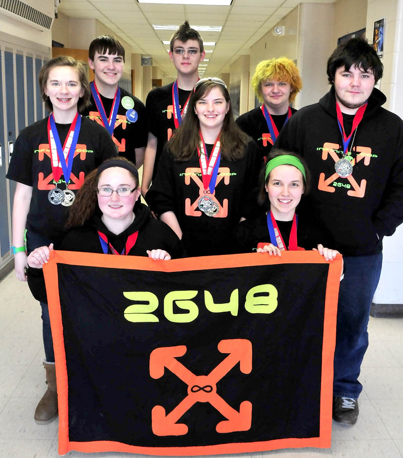 Members of the Messalonskee High School 2648 FIRST Robotics club at the Oakland school on Monday. Co-captains McKenzie Brunelle, left front, and Sabine Fountaine, hold the team banner along with members, from left, Taylor Ferguson, Robert Klein, Amy Pinkham, Brady Snowden, Bradley Bickford and Justin Shuman. The team won first place recently in regional competition and will advance to the world championship.