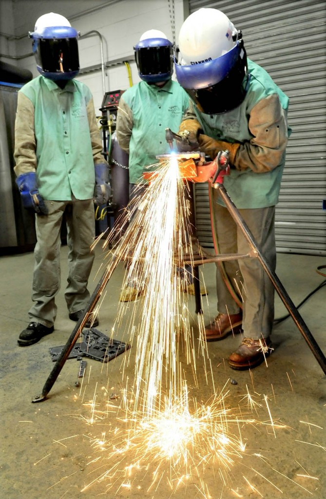 Skowhegan Area High School student Sarah Finnemore uses a cutting torch to cut steel at the Cianbro company welding training center. Waiting their turn are Cody Bailey, left, of Carrabec High School and Devon Blodgett of Valley High School.