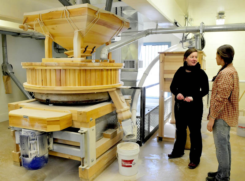 Amber Lambke, left, owner of Maine Grains, and head miller Julie Zavage discuss an order of flour being ground in the stone mill, left, at the Somerset Grist Mill in Skowhegan on Thursday.