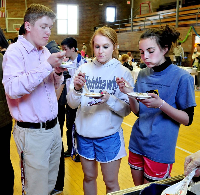 """Maine Central Institute students from left, Dylan Maloon, Courtney Fowler and Hailey Stewart sample a pork and shrimp dish during the International Food Festival in Pittsfield on Saturday. Between mouthfuls Fowler said the food was """"real good."""""""