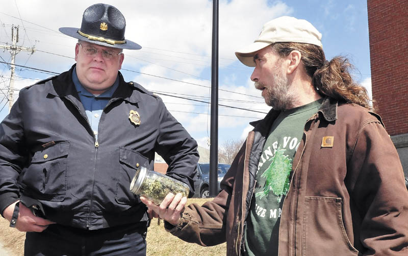 Marijuana advocate Donald Christen shows a jar of marijuana to Skowhegan Deputy Police Chief Dan Summers during the Patriots Day