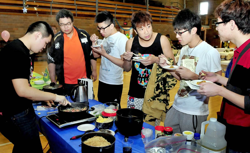 Maine Central Institute students line up to try the Thai fish plate being prepared by Joseph Yeh during International Food Festival in Pittsfield on Saturday.