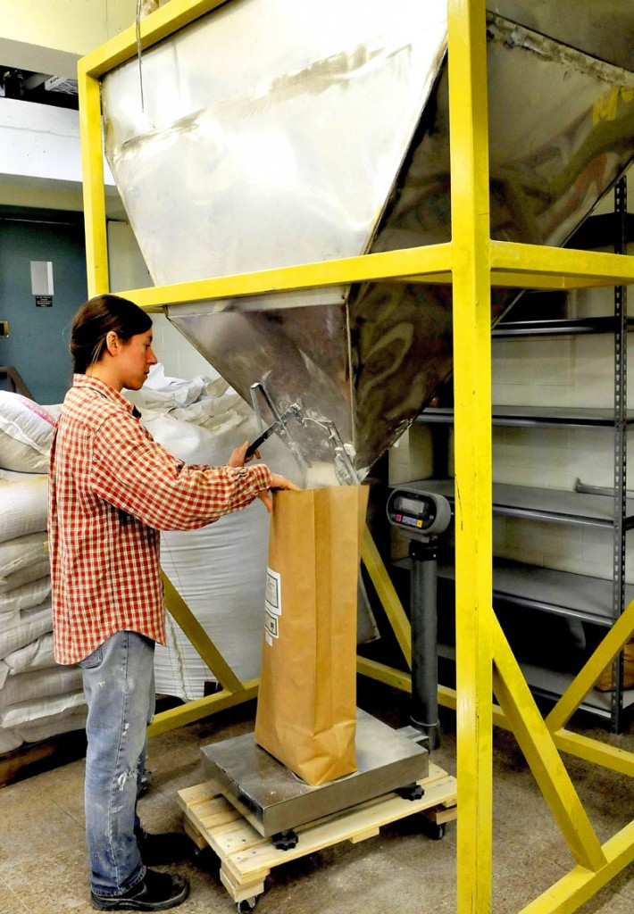 Head miller Julie Zavage bags flour pouring from a hopper at the Maine Grains business in Skowhegan on Thursday.