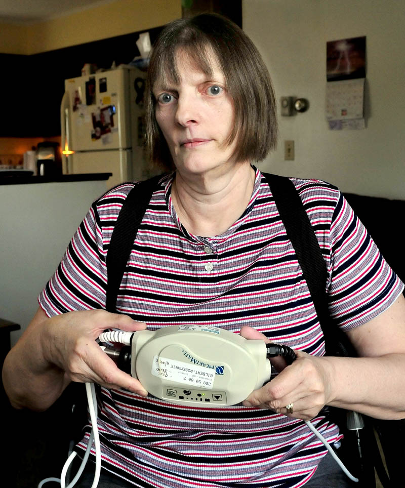 Rosemarie Gilbert, of Winslow, holds the ventricular assist mechanical pump that helps keep her heart working. Gilbert suffers from congenital heart disease and is awaiting a transplant.